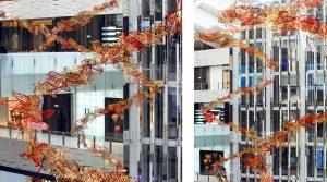 Attachées à une structure placée à 24m de hauteur, trois installations suspendues composées de plumes or et rouges envahissent l'espace de l'atrium, dans un mouvement qui rappelle le vent de Noël balayant L'AVENUE.
