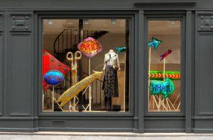 Mars 2017 – Boutique » CHLOÉ STORA » . Les structures en bois brut qui soutiennent l'ensemble de ces pancartes textiles accentuent l'effet de profusion et de décalage de la composition face à un environnement parisien très « élégant » et normatif.