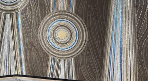 Cette alcôve de mosaïques vibre tel un écrin en mouvement, invoquant nature et mystères. Cette fresque murale, composée de cercles concentriques, symbolisent des points d'eau, la terre et les sites rocheux.