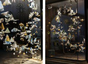 Hiver 2017 – Relais & Châteaux – Vitrines de Noël – Décor de vitrines de la boutique avenue de l'Opéra à Paris. L'or scintille et se mêle aux cartes géographiques, conférant à l'installation un aspect festif. ©Géraldine Brunel