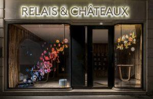 Printemps 2018 – Relais & Châteaux – Vitrines de Printemps – Décor de vitrines de la boutique avenue de l'Opéra à Paris. La boutique Relais & Châteaux salue le printemps avec une envolée d'hirondelles et de fleurs qui annonce l'arrivée des beaux jours.