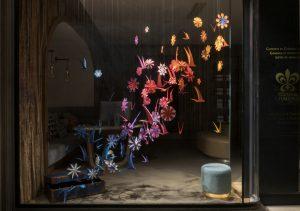 Printemps 2018 – Relais & Châteaux – Vitrines de Printemps – Décor de vitrines de la boutique avenue de l'Opéra à Paris. L'installation, entièrement faite de papier à la main, développe un dégradé de couleur qui attire l'attention de loin, tandis que, lorsqu'on s'approche, on lit le détail des fleurs et des oiseaux qui le composent.