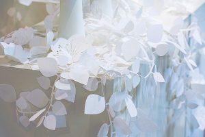 JCricket – 2018. Entre impressions et découpes de papier, lumière et supports blancs façonnent un décor pur et simple où s'installe une montagne de valises stylisées.