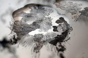 Angèle Guerre, plasticienne, 2015 à 2016, «Miroir, Étain», dimensions 91,5cm x 125 cm. Miroir en étain, papier et encre de chine. En retirant la matière, l'artiste fait apparaître des couches de paysage. Son travail relève d'une forme d'archéologie. Elle creuse la matière pour faire apparaître différentes strates d'un monde purement minéral et végétal.