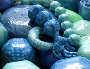 """Emilie Faïf, visual artist, April 2021, Mobile textile installation """"On n'est jamais trop petit pour lire"""", Pas-de-Calais. These large rounded cushions are destined to be manipulated according to the needs of collective or small group readings. The colorful shapes, all unique, create a joyful appeal for the little ones."""