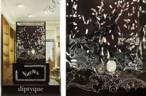 This decor is dedicated to showcase the new Volute perfume, an oriental and woody fragrance. Based on the memories of a boat trip to Saigon by Yves Coueslant, Volute mixes the waves' foam, smoke rings and smoke from liners. This imaginary world evokes the peaceful and sober image of Diptyque itself: the black and white decor is animated by white confettis and extended to the glass windows by carved dot pattern. Three black candlesticks enlighten the three Volutes bottles.