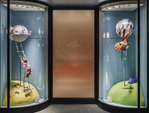 Soline d'Aboville, scenographer, January 2019, On hour way home from school, Hermès store, Genève. A railway guides one through magic worlds where hot-air balloon are trees, barques are runner beans, where planets are made out of ice-cream or coco-nuts. Each decor shows colorfull and eye-catching mini-worlds telling harebrained tales…