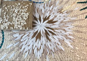 Mathilde Jonquière, mosaïste, Juin 2019, Triptyque Céleste. La mosaïque est composée de tesselles d'or cuivrées riches et profondes et de tons plus neutres (lin, sable, terre d'ombre) symbolisant la trame du fond d'une tapisserie sur laquelle on brode.
