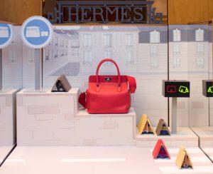 Printemps 2015 – Hermès – la Flânerie – Décor des vitrines du réseau des boutiques suisses. Ces décors de vitrine nous emmènent au marché : les soies deviennent des épices, les accessoires poussent au rayon plantes d'appartement, les chaussures grillent dans une rôtissoire et les ceintures se glissent dans un véritable cabinet de curiosité ambulant.