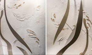 Soline d'Aboville, scénographe, juin 2021, vitrines Paradis été 21, Maison Hennessy, Hôtel Lutetia, Paris. Conçu comme une sorte de tableau et largement inspiré des lignes à la fois arrondies et tendues du flacon iconique, le décor est constitué d'une série de lames présentées en apesanteur devant une création d'Anne Lopez en stuc blanc et or.